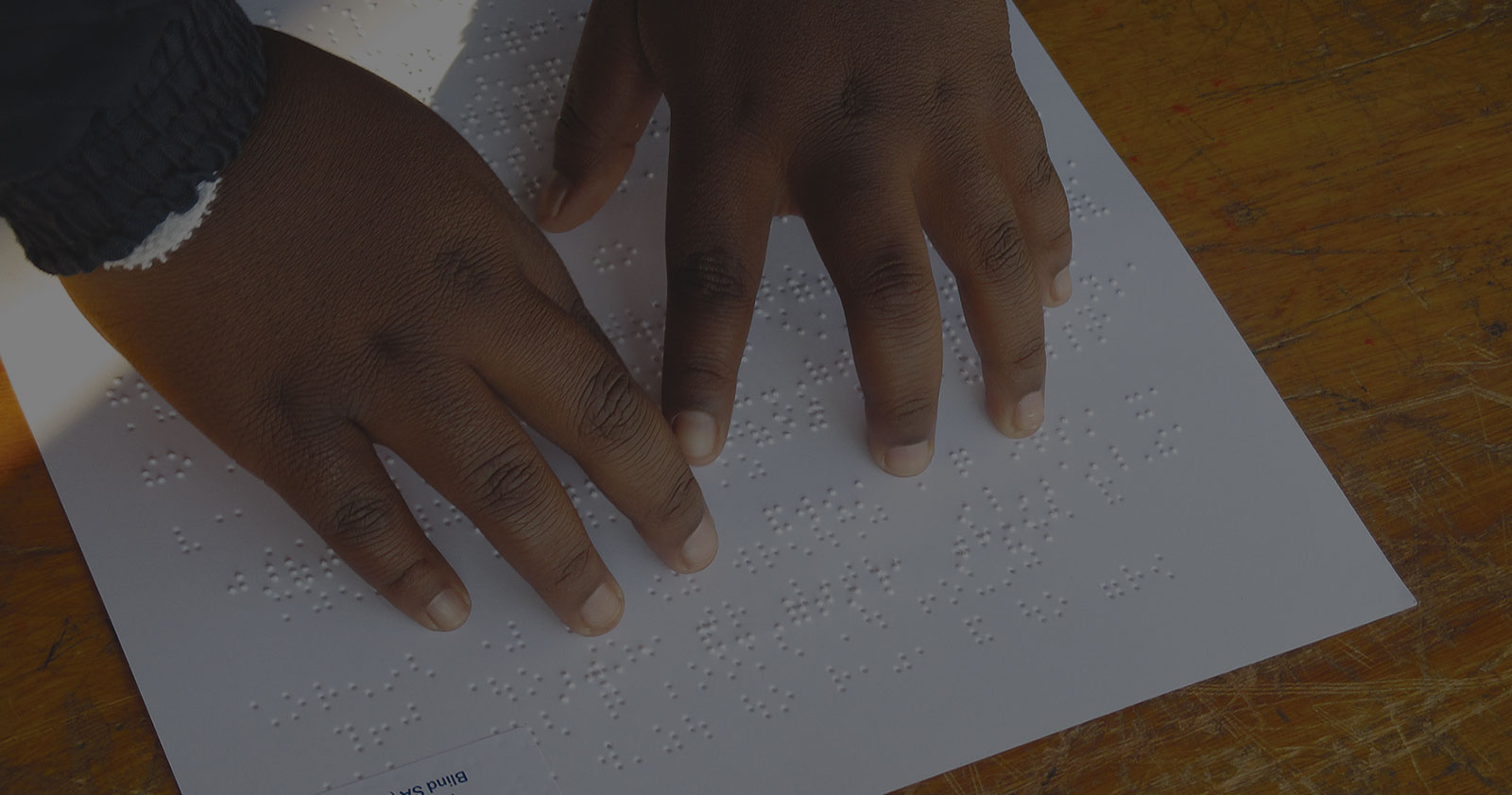 Little boy's hands, reading a braille page on a scratched school desk.