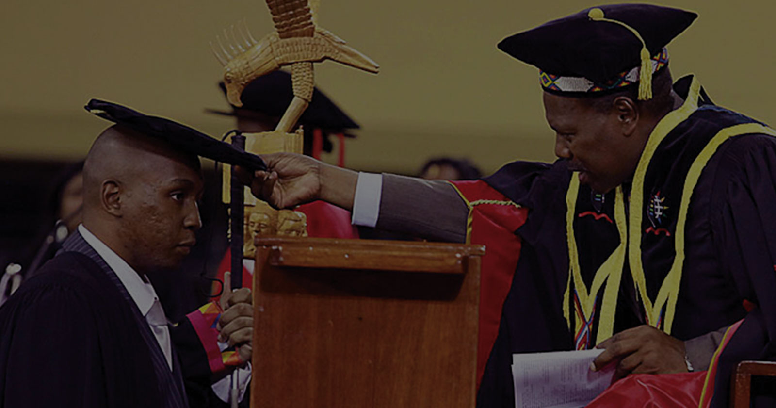 Blind student wearing academic gown and cap, graduating at university.