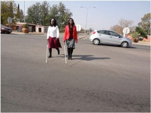 Two women with canes, crossing road as part of mobility training.