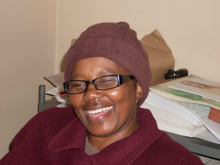 Blind SA employee, Victoria, sitting at her desk with a cheerful smile on her face.